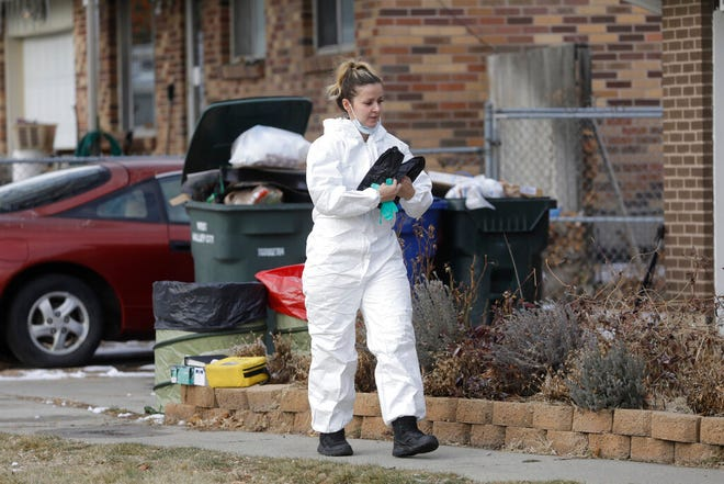 A member of the crime lab walks in front of a home Tuesday, Dec. 31, 2019, in West Valley City, Utah. A Utah mother is suspected of killing her 4-year-old daughter, The woman knocked on her neighbor's door in a Salt Lake City suburb early Tuesday morning and told them she had killed her daughter, West Valley City police said in a news release. Officers went to the house and found the woman waiting on the porch and the dead child in the basement of her home. (AP Photo/Rick Bowmer)