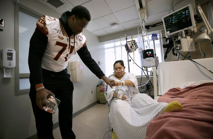Florida State offensive lineman Chaz Neal bumps fists with Las Palmas pediatric intensive care patient Michelle Rodriguez, 15.