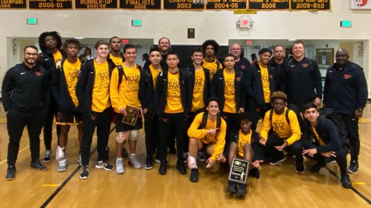 The Oxnard High boys basketball team poses with the championship plaque of the 56th annual Ventura Kiwanis Tournament on Monday night.