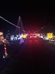 Cars drive down the Kupers Christmas lane lined with lights and decorations in December 2019.