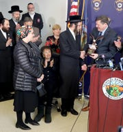 Town of Ramapo Supervisor Michael Specht presents Monsey resident Josef Gluck with an award during a news conference at Ramapo Town Hall Dec. 31, 2019.