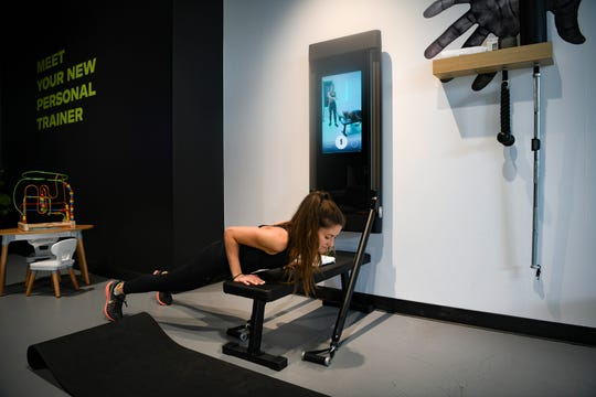 The Tonal home gym, as seen here in a Los Angeles showroom with reporter Carly Mallenbaum, comes with a screen and has accessories including a bench, mat and smart weight handles.