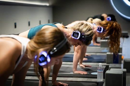 At VibeFlow Yoga, participants wear headphones so they can hear their instructor over the sound of vibrating plates.