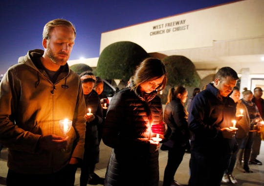 Church and community members, including Matt Pacholczyk, left, and his wife, Faith Pacholczyk, stand outside West Freeway Church of Christ for a candlelight vigil on Monday night in White Settlement, Texas.
