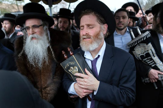 Community members, including Rabbi Chaim Rottenberg, left, celebrate the arrival of a new Torah on Dec. 29, 2019, near the rabbi's residence in Monsey, N.Y. A day earlier, a knife-wielding man stormed into the home and stabbed multiple people as they celebrated Hanukkah in the Orthodox Jewish community.