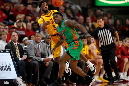 Iowa State guard Tre Jackson, left, saves the ball from going out of bounds as Florida A&M guard Nasir Core, right, defends during the first half of an NCAA college basketball game Tuesday, Dec. 31, 2019, in Ames, Iowa. (AP Photo/Matthew Putney)