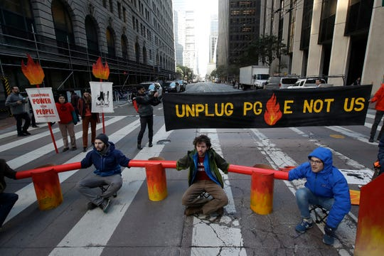 Protesters block traffic on Beale Street where a Pacific Gas & Electric building is located in San Francisco, Monday, Dec. 16, 2019.
