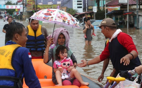 A rescue team talks to a girl in floodwaters at Jatibening on the outskirt of Jakarta, Indonesia, Wednesday, Jan. 1, 2020.