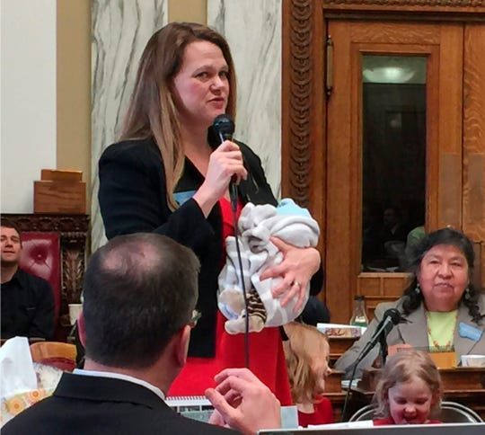 In this March 2017, photo, provided by Rep. Kimberly Dudik, Dudik speaks on the floor of the legislature holding her newborn son Marcutio in Helena, Mont.