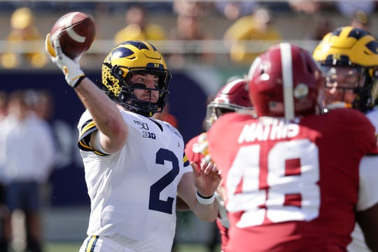 Michigan quarterback Shea Patterson (2) throws a pass as he is pressured by Alabama defensive lineman Phidarian Mathis (48).