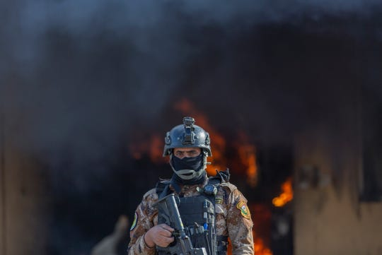 An Iraqi soldier stands guard Wednesday as smoke rises from a fire set by pro-Iranian militias in the U.S. Embassy compound in Baghdad, Iraq.