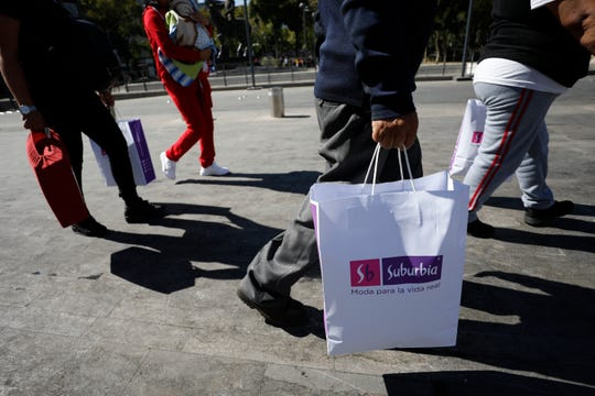 Shoppers carry purchases in paper and cloth bags as they walk in central Mexico City, Wednesday, Jan. 1, 2020.