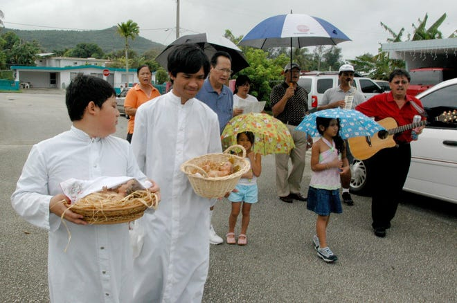 In this file photo, altar servers Christian San Agustin, left, and Aaron Salas take statues of the niño around the Hyundai Subdivision in Santa Rita.