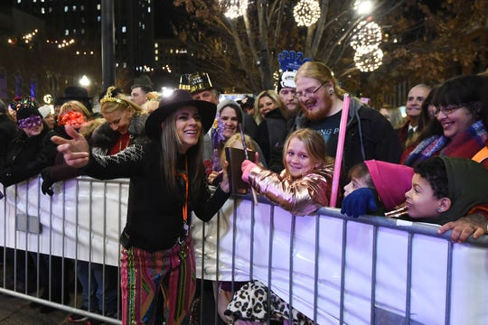 Diana Sosa, of the Bicho Brother's band, lets fans ring a cowbell during the band's New Year's Eve performance on Market Square on Tuesday, December 31, 2019.