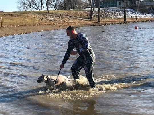 Brandon Sallee and his dog Brawny braved the cold water during the annual Polar Bear Dip fundraiser for cancer awareness on New Year's Day. Brawny likes the water, Sallee said.