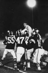 Hartford players carry Bob Larsen off the field following a game during his 15-year run as the school's head coach.