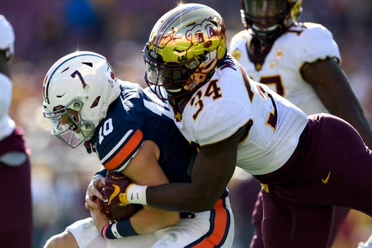 Jan 1, 2020; Tampa, Florida, USA; Auburn Tigers quarterback Bo Nix (10) scrambles with the ball as Minnesota Golden Gophers defensive lineman Boye Mafe (34) defends during the second quarter at Raymond James Stadium. Mandatory Credit: Douglas DeFelice-USA TODAY Sports