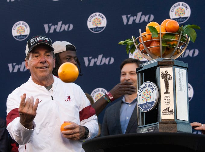 Alabama head coach Nick Saban tosses oranges from the Citrus Bowl trophy into the crowd after beating Michigan in the Citrus Bowl in Orlando, Fla., on Wednesday January 1, 2020.
