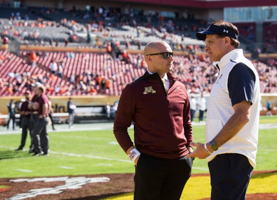 Minnesota head coach P.J. Fleck and Auburn head coach Gus Malzahn talk during warm ups before the Outback Bowl at Raymond James Stadium in Tampa, Fla., on Wednesday, Jan. 1, 2020.
