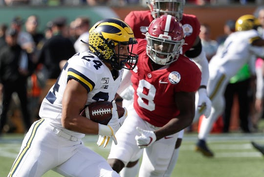 Michigan running back Zach Charbonnet gets past past Alabama linebacker Christian Harris during the Citrus Bowl.