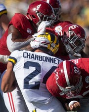 Michigan running back Zach Charbonnet (24) is stopped by Alabama linebacker Christopher Allen (4), defensive back Xavier McKinney (15) and linebacker Anfernee Jennings (33) in the Citrus Bowl in Orlando, Fla., on Wednesday January 1, 2020.