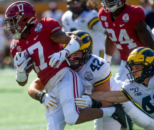 Alabama wide receiver Jaylen Waddle (17) is stopped by Michigan defensive lineman Ben Mason (42) on a kick return in the Citrus Bowl in Orlando, Fla., on Wednesday January 1, 2020.