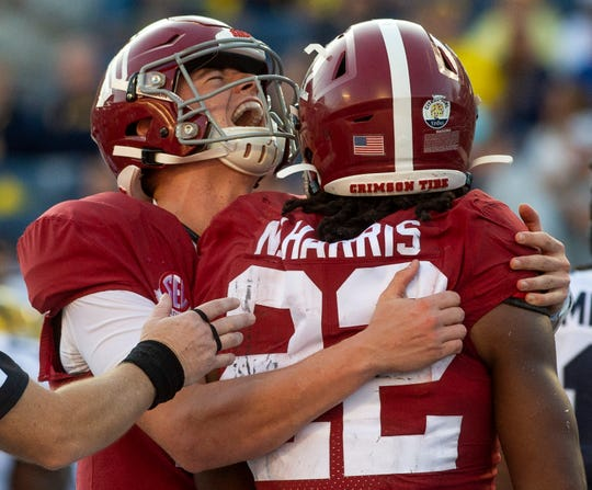 Alabama quarterback Mac Jones (10) his Alabama running back Najee Harris (22) after Harris' late touchdown against Michigan in the Citrus Bowl in Orlando, Fla., on Wednesday January 1, 2020.