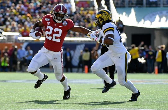 Jan 1, 2020; Orlando, Florida, USA; Alabama Crimson Tide running back Najee Harris (22) runs with the ball around Michigan Wolverines defensive back Josh Metellus (14) during the first half at Camping World Stadium. Mandatory Credit: Jasen Vinlove-USA TODAY Sports