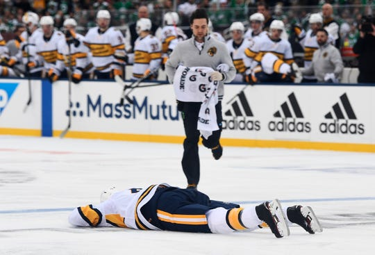 Predators defenseman Ryan Ellis is down on the ice after being elbowed by Stars right wing Corey Perry during the first period of the 2020 NHL Winter Classic at the Cotton Bowl in Dallas, Texas, on Jan. 1.