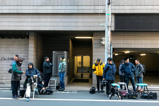 Journalists stake out at the back entrance of a building which houses an office of Junichiro Hironaka, a lawyer for Nissan's former Chairman Carlos Ghosn, in Tokyo Tuesday, Dec. 31, 2019.