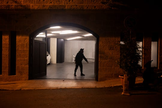A security guard stands in the garage at the residence of former Nissan Chairman Carlos Ghosn on Monday, Dec. 30, 2019 in Beirut, Lebanon. A close friend says Ghosn, who is awaiting trial in Japan, has arrived in Beirut.