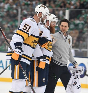 Nashville Predators defenseman Ryan Ellis (4) is helped off the ice after being elbowed by Dallas Stars right wing Corey Perry (10) during the first period of the 2020 NHL Winter Classic at the Cotton Bowl in Dallas, Texas, Wednesday, Jan. 1, 2020.