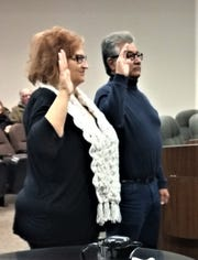 Carrizozo Council members Cynthia Johnson and Ronald Beltran raise their hands to swear their oaths of office.