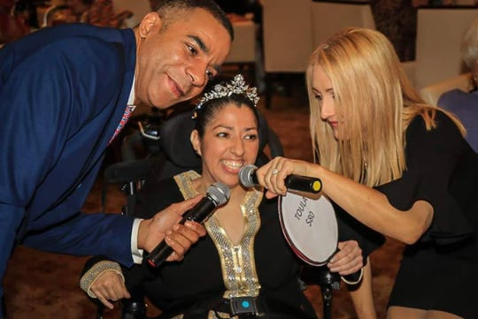Angel View client Maria talks with emcees Bryan Gallo and Thalia Hayden at a previous event.