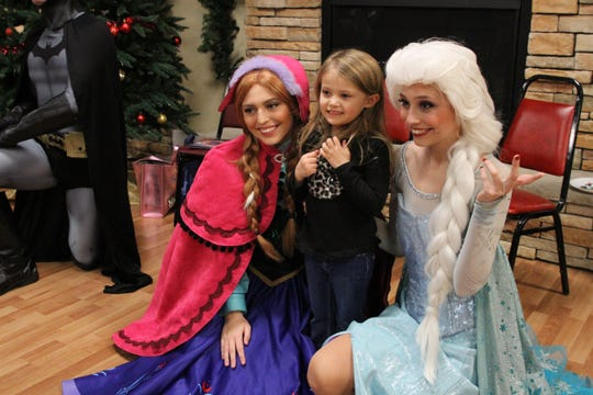 Charlotte Hirt of Port Clinton poses for a photo with Princesses Elsa and Anna at the Minnow Drop kids party at the Knights of Columbus Hall.
