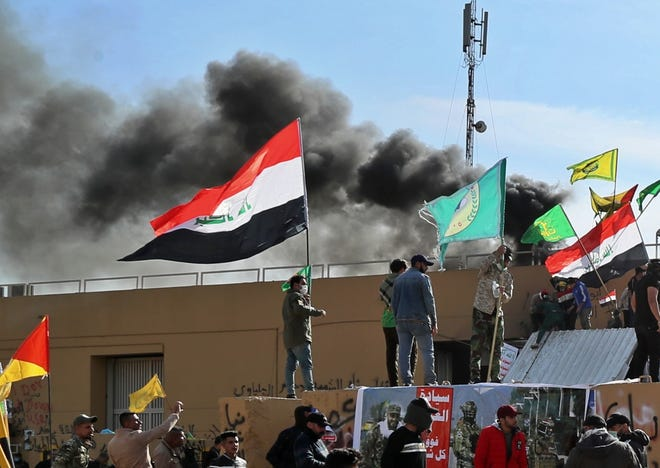 Smoke rises after pro-Iranian militiamen and their supporters set a fire in front of the U.S. embassy in Baghdad, Iraq, Wednesday, Jan. 1, 2020. U.S. troops have fired tear gas to disperse hundreds of pro-Iran militiamen and other protesters who were gathered for a second day outside the American Embassy compound in Baghdad. (AP Photo/Khalid Mohammed)