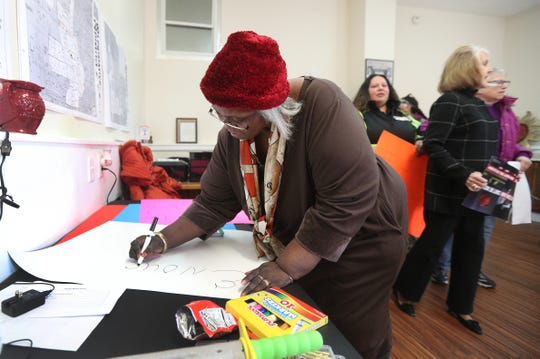 Deborah Smith, president of the Edgerton Neighborhood Association, makes signs to carry in an anti-violence peace march along Lyell Ave.