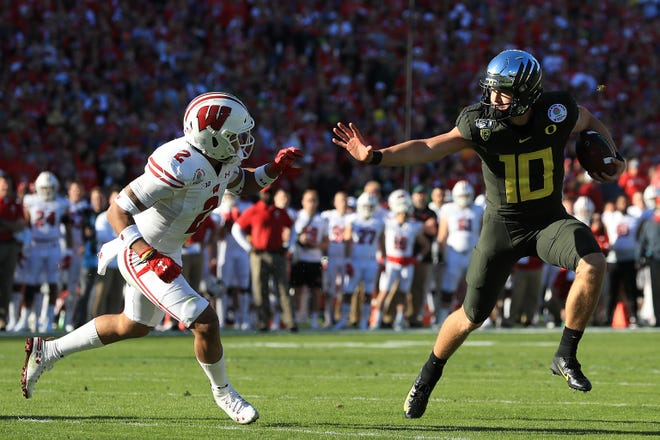 Justin Herbert #10 of the Oregon Ducks runs the ball against Reggie Pearson #2 of the Wisconsin Badgers during the first quarter in the Rose Bowl game presented by Northwestern Mutual at Rose Bowl on January 01, 2020 in Pasadena, California.