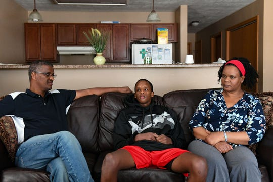 Mhiretab Tsegaye and his parents sit on the couch on Tuesday, Dec. 31, at their home in Sioux Falls. Dejane was released from the hospital after two months following a car crash in November.