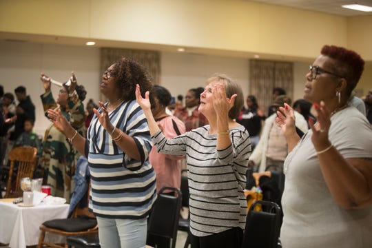 Members of Joshua Harvest Church praise during a New Year's Eve service Tuesday night at Claymore Community Center.