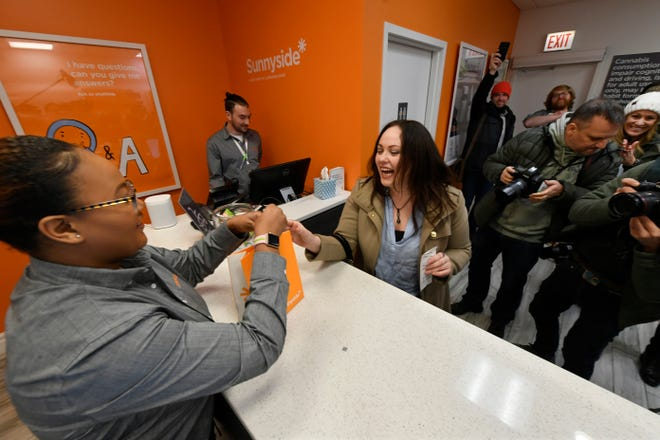 Jackie Ryan, right, of Forest Park, Ill., becomes the first person in Illinois to purchase recreational marijuana as she purchases marijuana products from employee Brea Mooney left, at Sunnyside dispensary Wednesday, Jan. 1, 2020, in Chicago.