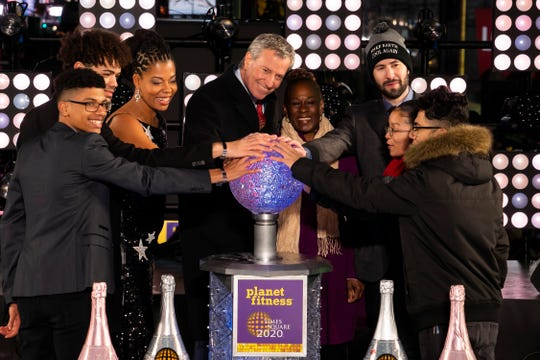 New York Mayor Bill de Blasio, fourth from left, starts the countdown to midnight on stage at the Times Square New Year's Eve celebration, late Tuesday, Dec. 31, 2019, in New York.
