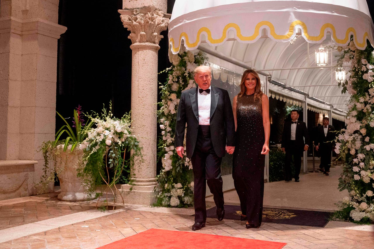 President Donald Trump and first lady Melania Trump arrive for the annual New Year's Eve party at Mar-a-Lago in Palm Beach, Fla., on Dec. 31, 2019. She is wearing a Givenchy gown, sparkly gold on top, sparkly black on the bottom.