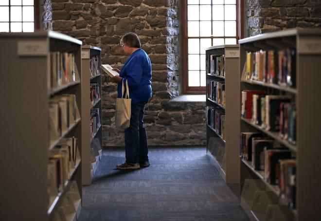 Ann Rasmussen of Kaukauna browses the fiction section inside the Kaukauna Public Library in 2017.