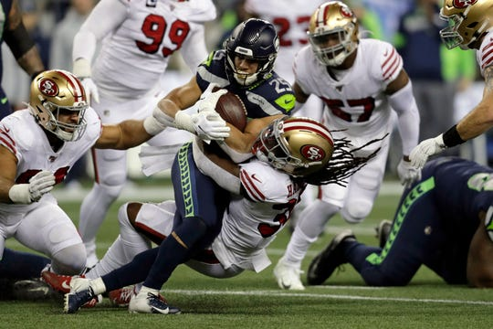 Seattle Seahawks running back Travis Homer (25) is brought down by San Francisco 49ers' Marcell Harris on a carry during the first half of an NFL football game, Sunday, Dec. 29, 2019, in Seattle.