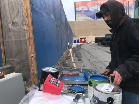 "Brad McGarghan prepares to apply blue paint over graffiti at the Burlington CityPlace site on Jan. 2, 2020. Applying paint in 34 degrees is do-able, McGarghan said, ""but it's still too cold."""