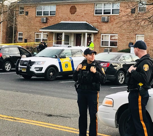 Police officers on Thursday stand outside the scene of an apparent murder-suicide at the Willow Pointe apartment complex in Burlington Township.