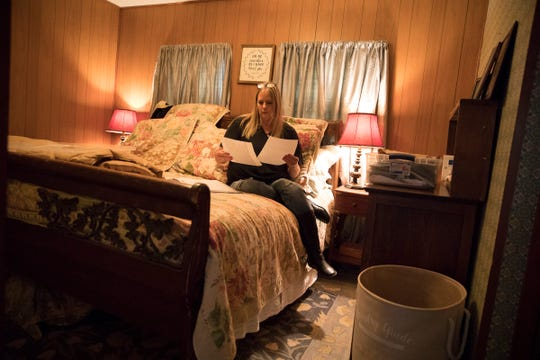 """Karen Bower looks through a tote of different hand-written versions of her book she kept to help her in her writing process of """"Loving My Addict: A Mother's Journey"""" in her bedroom in Frankfort, Ohio."""