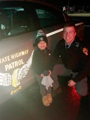 """In this Sunday, Dec. 29, 2019, photo provided by Leah Sharkey, her son and the Ohio State Highway Patrol Trooper Alex Schlottag pose for a photo, west of Sandusky, Ohio. The Ohio state trooper reunited the young boy with his favorite stuffed toy, """"booboo,"""" that was dropped out of a car window on a highway."""