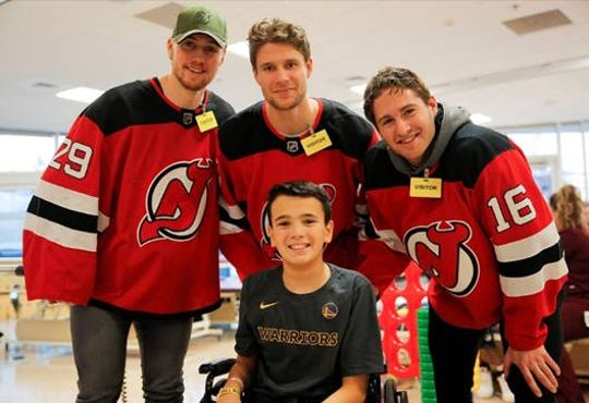 RWJ University Hospital-New Brunswick/BMSCH and Children's Specialized Hospital enjoyed some holiday cheer on Tuesday, Dec. 17, as New Jersey Devils John Hayden, Jesper Bratt, Jesper Boqvist, Kevin Rooney, Mackenzie Blackwood and Pavel Zacha spent the afternoon interacting with patients and staff during their annual visit. (Left to right) Mackenzie Blackwood, Pavel Zacha, and Kevin Rooney visit with Brandon Rifflard, a patient at Children's Specialized Hospital.